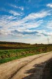 弯曲在绿色领域的土路在蓝色多云天空下 农村的横向 库存图片