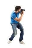 弯曲拍照片有数字照相机侧视图的年轻人 图库摄影