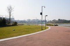 弯曲有现代大厦的湖边红色道路在s的距离 免版税库存图片