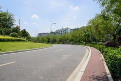弯曲涂柏油的路在城市在晴朗的夏天中午 免版税库存照片