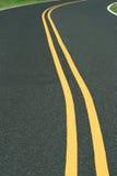 弯曲的双重线的路黄色 免版税库存图片
