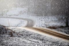 弯曲的和有风冷淡的土路 免版税库存照片