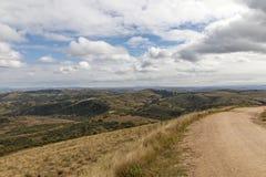 弯曲的土路通过反对冬天风景的干草 免版税图库摄影