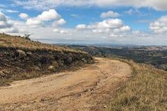 弯曲的土路通过反对冬天风景的干草 图库摄影