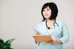 弯曲的女性护士站由笔直写结果在纸,在有听诊器的医学实验室外套在她的脖子上 免版税库存照片