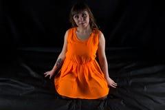 弯曲的妇女照片橙色礼服的 免版税图库摄影