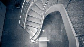 弯曲的扔石头的楼梯的单色图象在现代大厦的 免版税库存照片