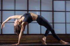 弯曲的旁边板条姿势年轻可爱的妇女,平衡pract 库存图片