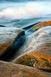 弯曲的海运向波浪扔石头 免版税图库摄影