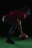 弯曲的美国橄榄球运动员拿着在草皮的一个球用两只他的手 库存图片