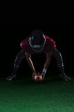 弯曲的美国橄榄球运动员拿着在草皮的一个球用两只他的手 免版税图库摄影
