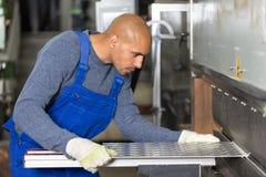 弯曲的金属板的工作者运行的机器 免版税库存图片
