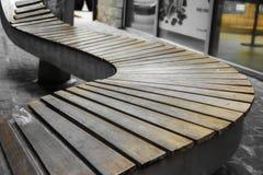 弯曲的长木凳在公园 免版税库存照片