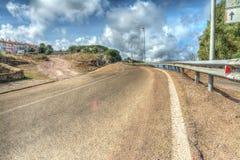 弯曲道路在hdr口气映射的多云天空下 免版税库存照片