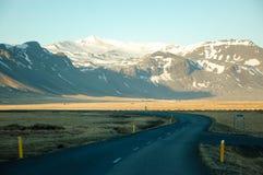 弯曲道路,种秣草地,山,晚上阳光,冰岛 图库摄影