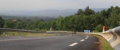 弯曲黑路,波纹白铁管和弯曲黑路,波纹白铁管和cevrons在法国中央高原在法国中央高原  库存照片