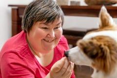弱智的妇女喂养一条狗 库存图片