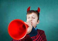 弹一个玩具喇叭的滑稽的顽皮男童在教室 免版税图库摄影