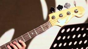 弹一把低音电吉他的一只男性手 特写镜头 在一个音乐主题的英尺长度 股票视频