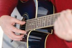 弹一把古典吉他的吉他弹奏者的细节 库存图片