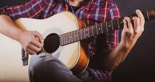 弹一把声学吉他的人在一间录音室 免版税库存图片