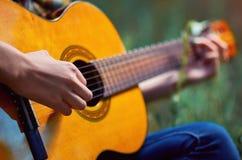 弹一把声学吉他的女孩` s手的特写镜头 免版税库存图片