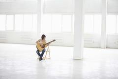 弹一把声学吉他的妇女在宽敞仓库里 免版税库存图片