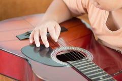 弹一把声学吉他的男孩 免版税库存照片