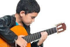 弹一把声学吉他的逗人喜爱的西班牙男孩 免版税库存图片