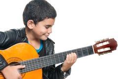 弹一把声学吉他的逗人喜爱的西班牙男孩 免版税库存照片