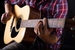 弹一把声学吉他的年轻人在演播室 免版税库存照片