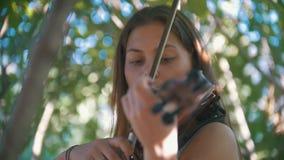 弹一把小提琴的女孩行家画象在公园夏日 股票视频
