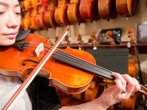 弹一把小提琴的妇女小提琴手在音乐商店 免版税图库摄影