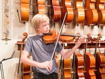 弹一把小提琴的男孩小提琴手在音乐商店 免版税库存照片