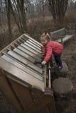 弹一把木琴的女孩在庭院里 免版税库存图片