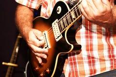 弹一把电吉他的一个人的特写镜头 库存照片