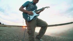 弹一把电吉他的人音乐家吉他弹奏者的剪影在日落靠近水 男性吉他弹奏者概念 股票视频