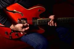 弹一把电吉他的人 特写镜头,没有面孔 免版税库存图片