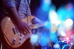 弹一把电吉他的吉他弹奏者的特写镜头在音乐会 免版税图库摄影