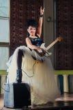 弹一把电吉他的一个女性吉他弹奏者的照片 免版税库存照片