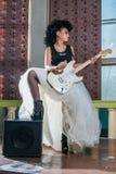 弹一把电吉他的一个女性吉他弹奏者的照片 免版税库存图片