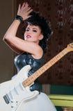 弹一把电吉他的一个女性吉他弹奏者的照片 库存图片