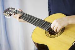 弹一把经典吉他的妇女 免版税库存照片