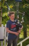 弹传统风笛的一个年轻scotish男孩在Portree,苏格兰 库存照片