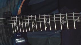 弹低音吉他的手特写镜头  股票 演奏在低音吉他的吉他弹奏者的男性手弦 音乐执行了  影视素材