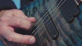 弹低音吉他的手特写镜头  股票 演奏在低音吉他的吉他弹奏者的男性手弦 音乐执行了  股票录像