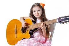 弹古典吉他的女孩隔绝在白色背景 免版税库存照片