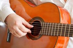 弹古典声学吉他的人 免版税库存照片
