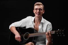 弹吉他和唱在黑背景的一个美丽和成功人歌曲 音乐,歌曲,岩石,流行音乐概念 免版税库存图片