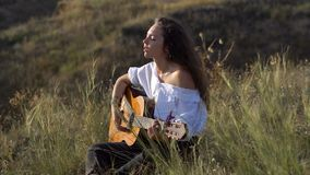 弹吉他和唱歌在海湾倾斜的领域的卷曲吉普赛深色的女孩  股票录像
